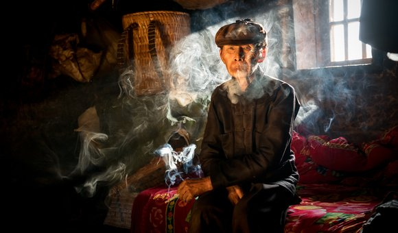A minority old man is smoking in his house in Pho Cao village, a small village in northern highland in Vietnam.