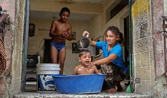 A Palestinian girl washes her brother during a sweltering heat wave, in Gaza city.