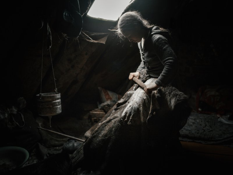 Both male and female Nenets wear hip-high reindeer skin boots consisting of an inner (Tobaki) and outer boot (Kisy). In this image, Nadia Serotetto is preparing hide for boots she'll sew using sinew as thread. 